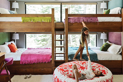 In this kids' bunk room, Maca Huneeus designed walnut beds with built-in storage and fabric headboards, and covered each one in hand-knit blankets by Marcela Rodriguez-Chile.