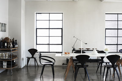 monochromatic dining room with concrete floors, white walls, and black Cherner chairs