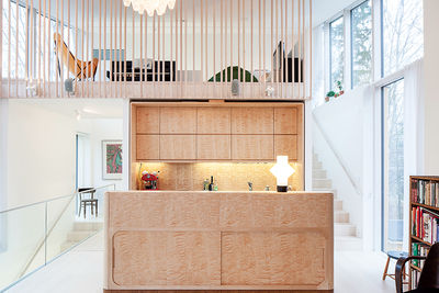 Modern home in Finland with sauna has custom birch cabinets and island in kitchen and a lofted family room