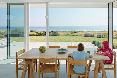 Modern Swedish family dream getaway with Ilva table and Carl Hansen & Søn chairs in dining area