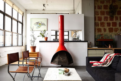 BoConcept sofa, restored steel chairs, and vintage 1960s fireplace in Brooklyn loft.