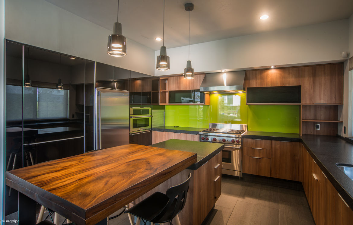 A green backsplash adds a touch of color in a kitchen with Electrolux and Wolf appliances.