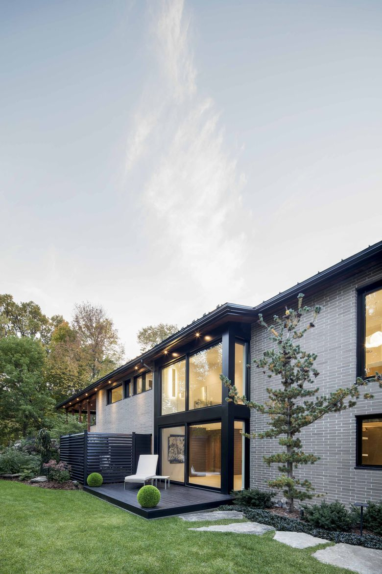 A glass wall lets sunlight into a midcentury renovation