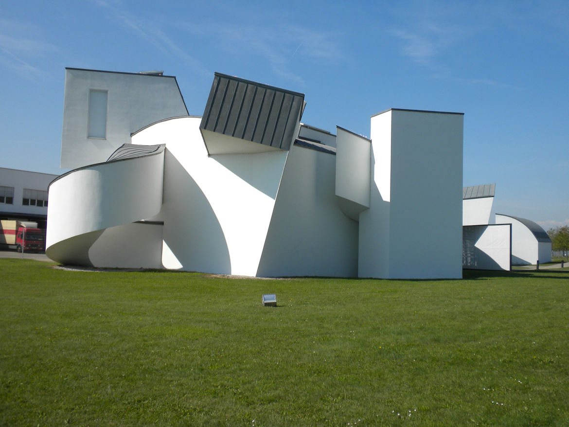 "The Vitra Design Museum is housed in this iconic building by <a href=""http://www.foga.com/"">Frank Gehry</a>. Built in 1989, it's the earliest non-factory structure on campus. The factory and the gate that he built in tandem with the museum all share the t"