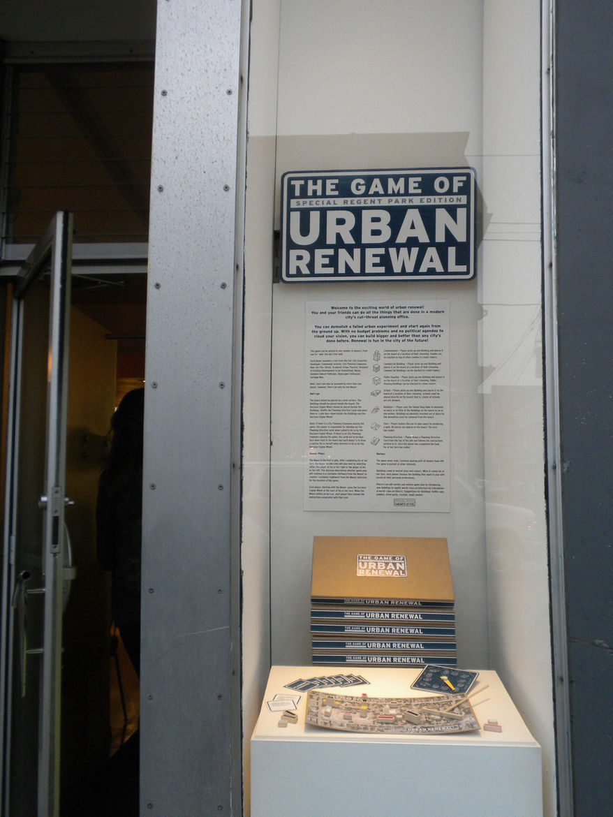 Now ready for a snack, we went in search of a coffee shop. Along our way, we spotted a strange little window opening. Inside, presented like an exhibition display, was <i>The Game of Urban Renewal</i>, a faux board game by artist Flavio Trevisan that chal