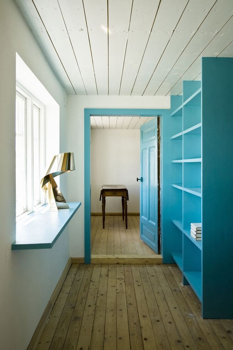 The library contains an extended windowsill that functions as a small desk. The two bedroom doors are visually integrated into the library. Photo by Laura Stamer.