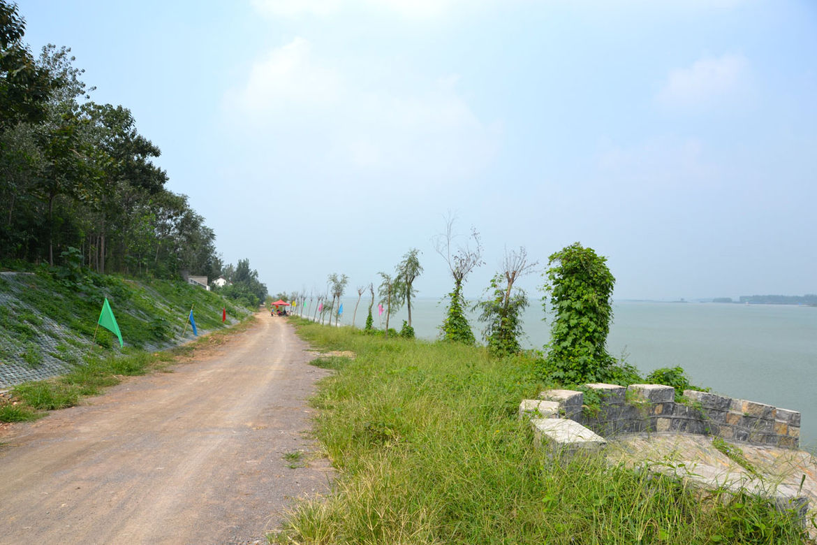 """Shahid spent a short time cycling along this small, local road that followed Hung-Tse Lake. """"I was happy riding along this dirt road as a break from the traffic flying by me on the national road that I've been following,"""" she says. Shahid's original plan"""