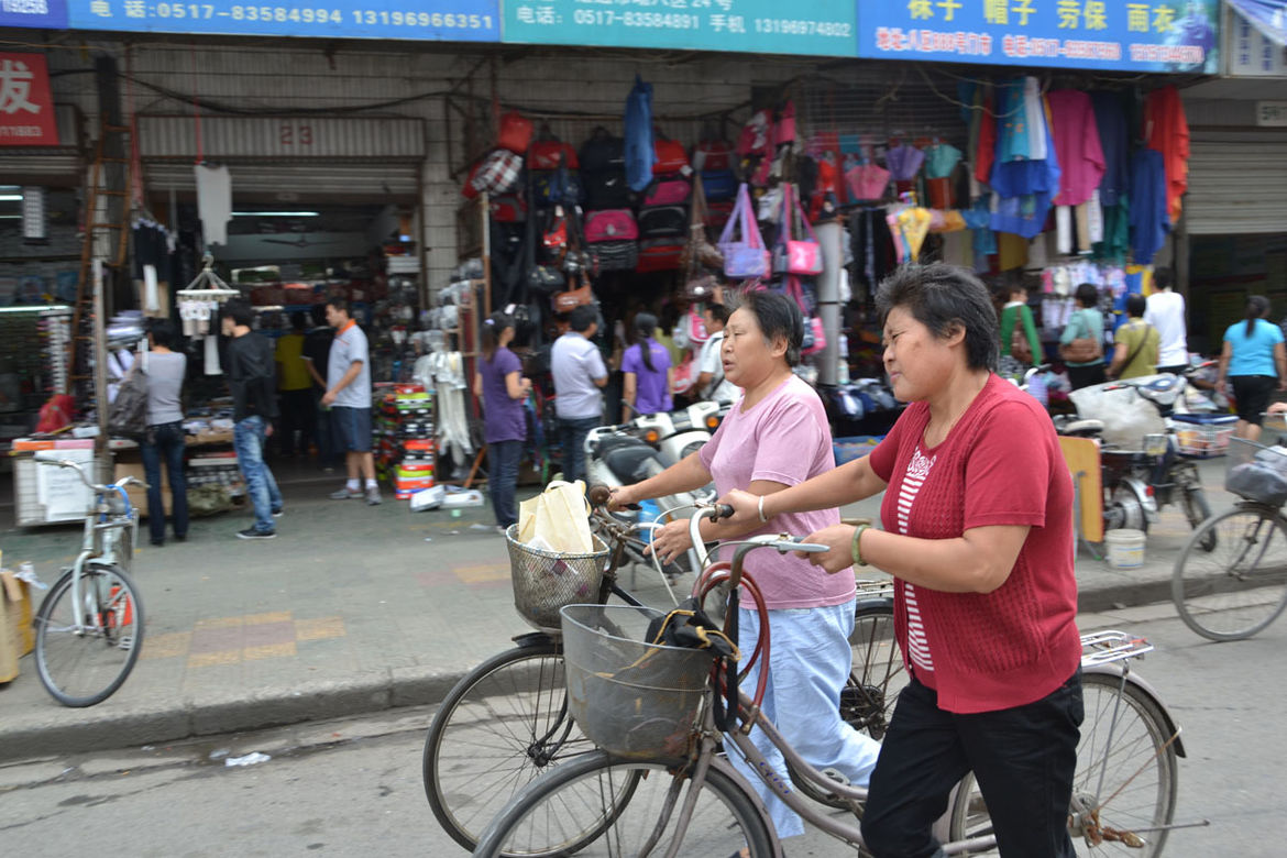 "In Huian, Shahid observed these two women walking their bikes instead of maneuvering them through the market and its crowds. ""The bikes were still useful for being big enough to open a crowd and for carrying newly bought goods,"" she says."