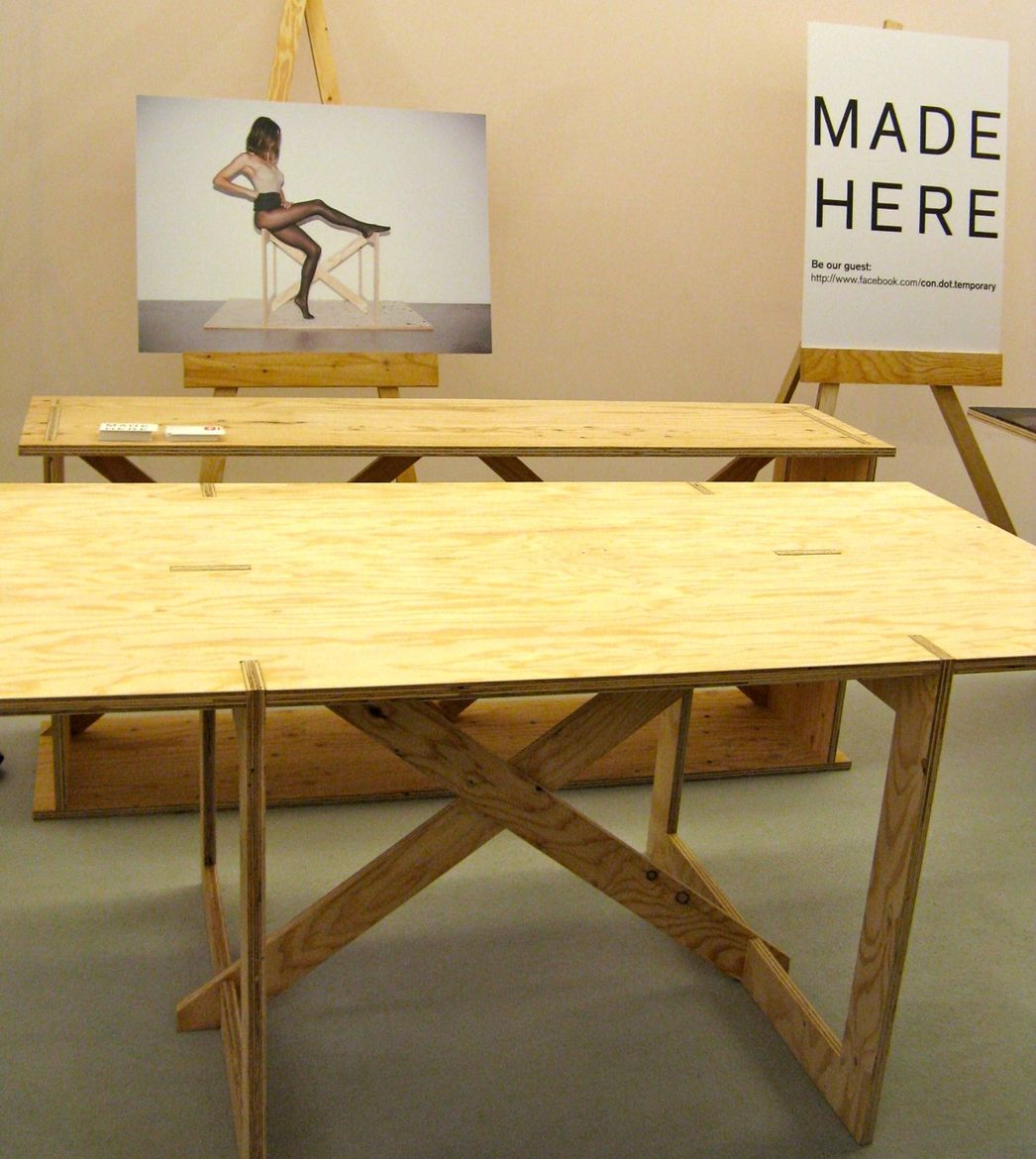 """This knock-down plywood table from Swiss designer <a href=""""http://www.colinschaelli.com"""">Colin Schaelli's</a> <a href=""""http://www.ownlineshop.com/ch_de/con-temporary-furniture.html"""">con.temporary</a> line is made in Japan, as the sign to the right indicat"""