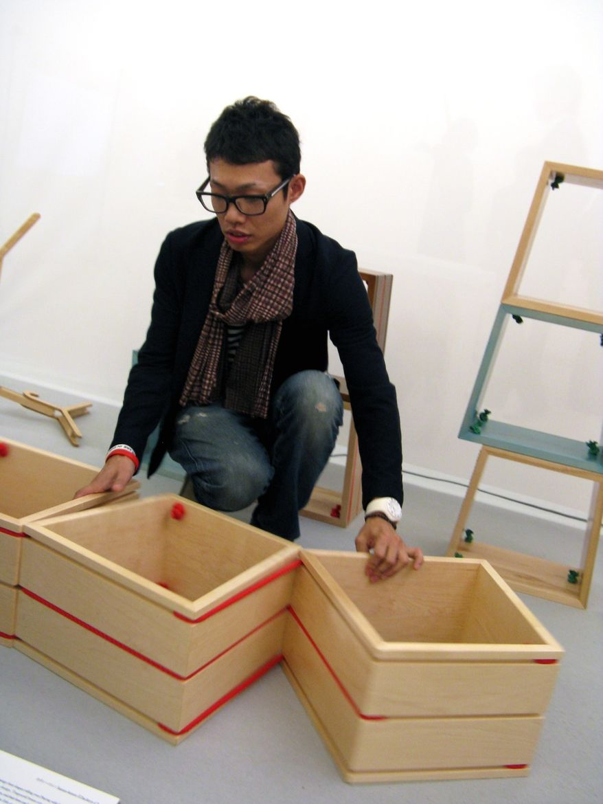 "Maple ""Clackety-Clack"" shelves by Kyoto-based <a href=""http://www.undo-design.com""> un-do Design</a> were inspired by the Japanese version of a Jacob's Ladder toy. Yasutaka Kimura—who collaborated on the concept with partner Rui Matsuo—demonstrates."