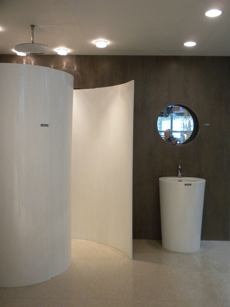 """<a href=""""http://www.hanwhasurfaces.com/"""">Hanwha</a>, creator of HanStone Quartz and Hanex Solid Surfaces, displayed an innovative use of solid surfaces that become a wrap-around, conch-like shower."""