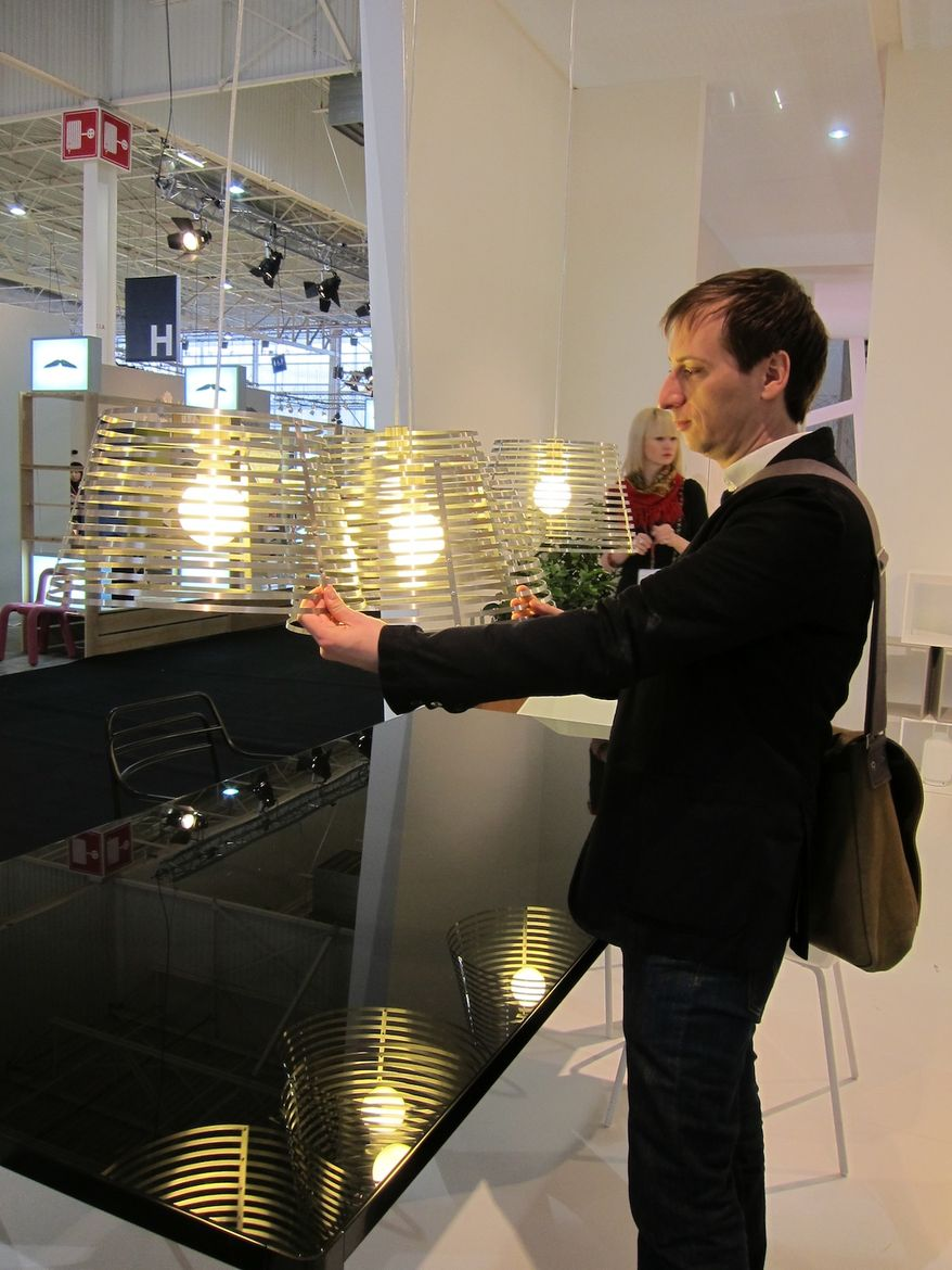 "Nigro demonstrates how his Stripes pendant lamps mesh together to form a ""composition of intersections."""