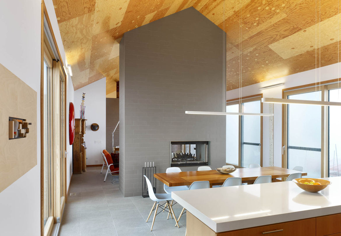The home primarily features two materials: tile and wood. In between the dining room and living room, a fireplace is wrapped in floor tiles of a similar color to those lining the ground. Above, Douglas Fir plywood lines the ceiling. Rendely wanted a ceili
