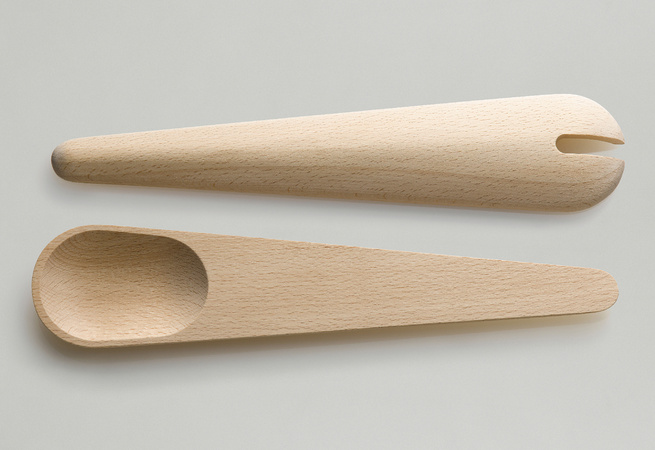 The Toss Around spoons differ from the Hang Around set as they are both spoons (rather than one spoon and one spatula), lack the slat in the back, and feature shallower spoons with a notch in one.