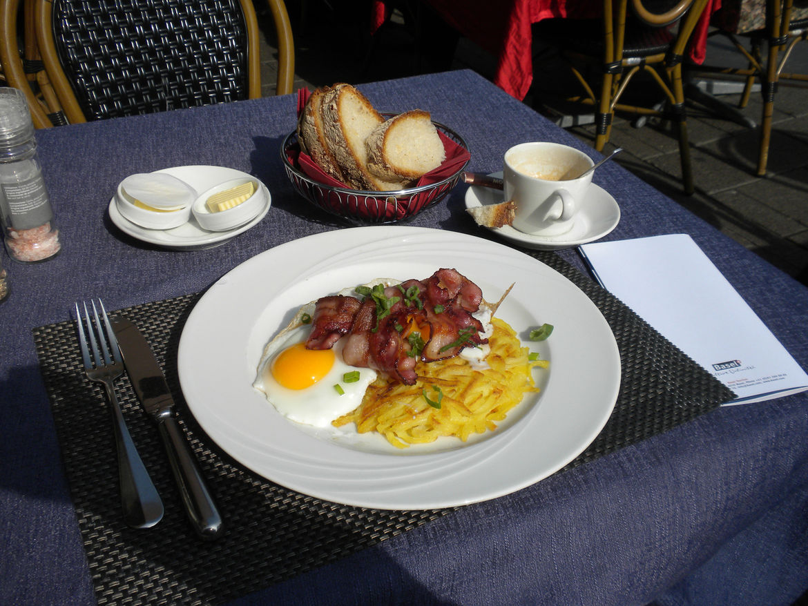 """At a restaurant across from City Hall, I enjoyed my first Swiss meal: fried eggs, bacon, and <i>rosti</i>. I was told by Diccon Bewes, a Brit turned Swiss who has lived in the country for years and recently penned the book <a href=""""http://swisswatching.wo"""