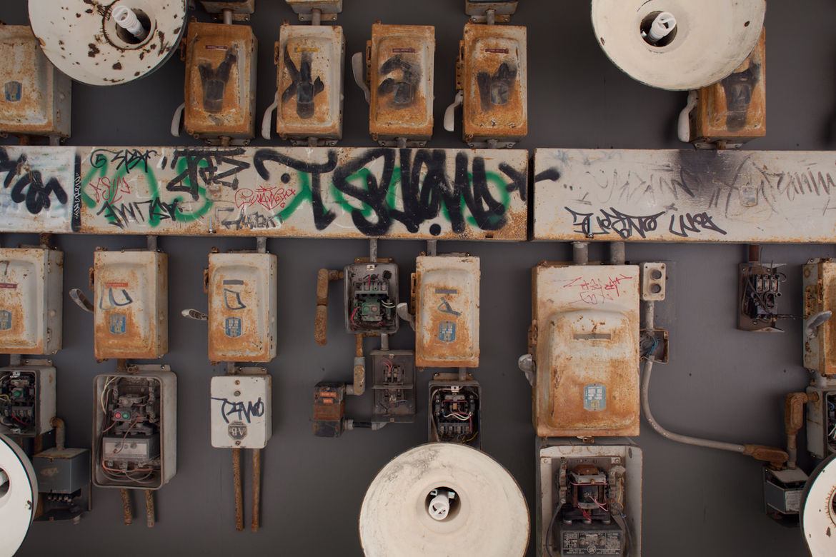 """Levitt and Touw covered the ceiling with artifacts found on the Brick Works site. """"We asked Matthew and his team to collect all the old power boards and lighting panels and made the ceiling out of them,"""" Levitt recalls. To provide light, they reactivated"""