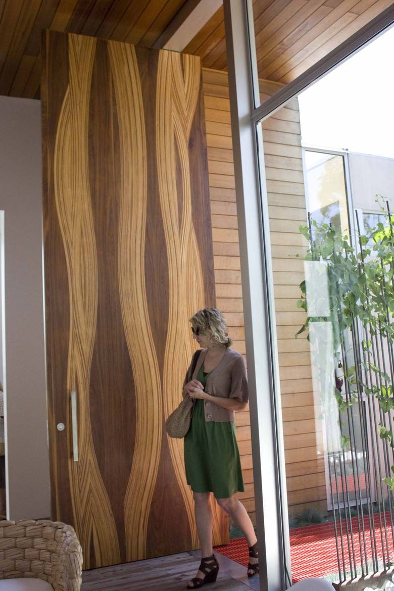 "The front door is an awe-inspiring 14-foot mixed wood creation made by L.A. custom door fabricators Real Door Inc. The wood used in making the door were mostly leftovers from the shop, says Dino of <a href=""http://www.realdoorinc.com/index.htm"">Real Door"