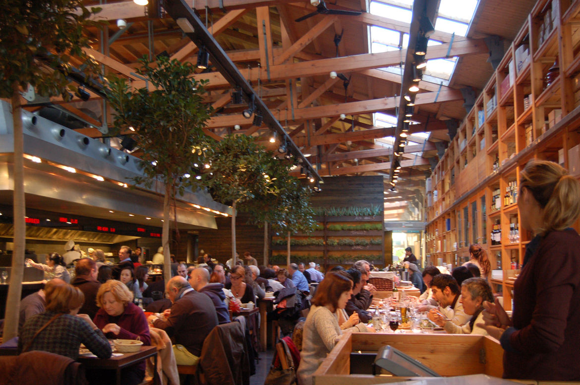 The interior of the restaurant at Mercat de Santa Caterina showcases the building's soaring roof line, massive beams, abundant natural light and near-floor-to-ceiling wood shelving.