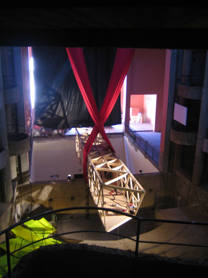 """Inside the main theater space was this massive bridge suspended by a red curtain and resting on a wall that divides the audience from the stage. But as the structure is unfinished, no stage exists. I talked with curator Nadim Samman and as he put it """"What"""