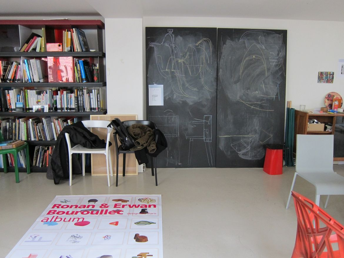 "Inside, the main floor of the studio is pleasantly cluttered with books, sketches, chair prototypes, finished products, and a blackboard where the brothers hash out their ideas. On the floor is a poster for their ""Album"" exhibition in Bordeaux. Downstairs"