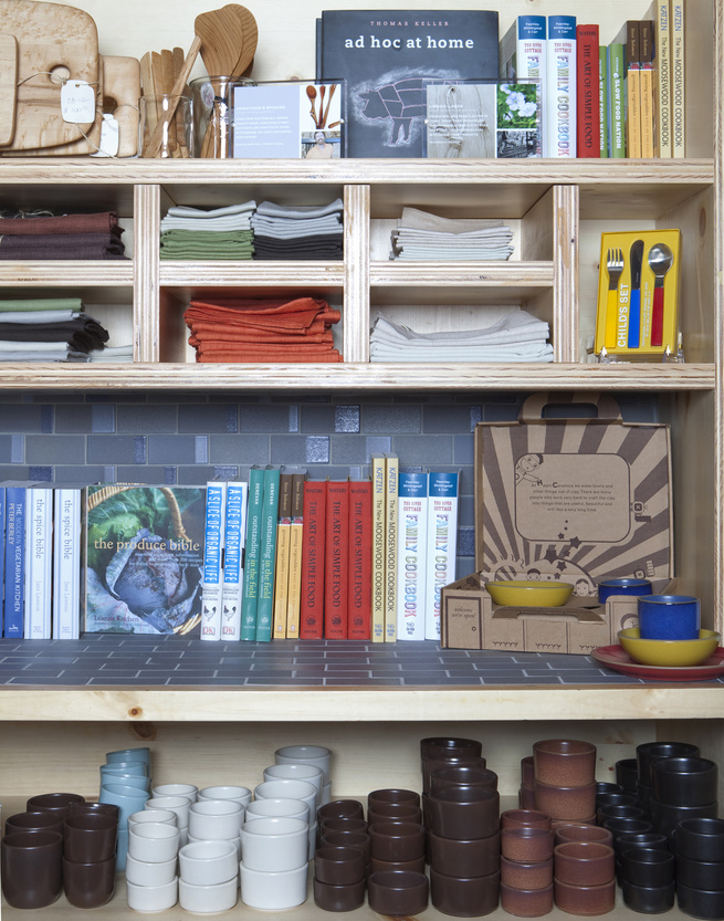 Tableware shares space with a curated collection of books, tea towels, and treasures for the home.