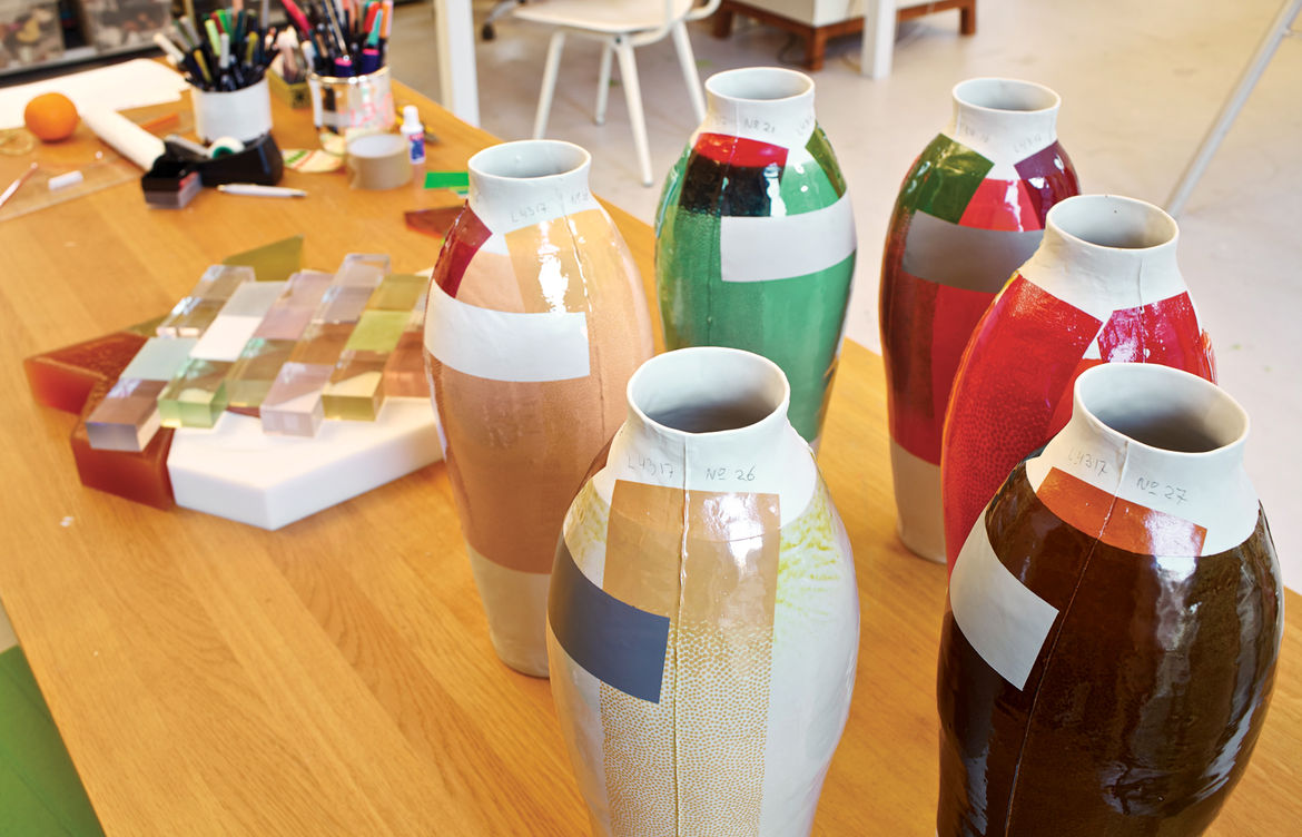 On a work table, a cluster of early color experiments foretells her <i>300 Unique Vases</i> project.