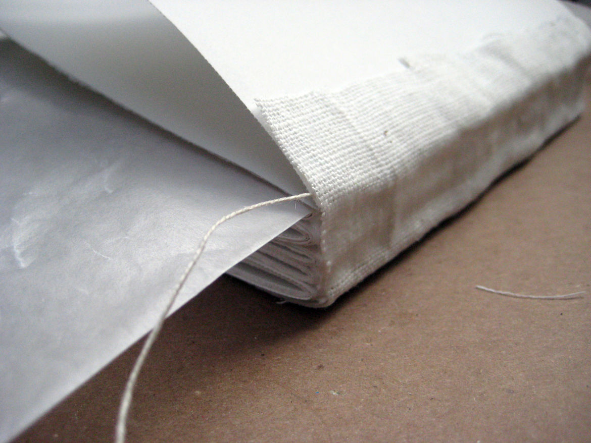 Now, remember those endsheets you set aside waaay back at the beginning of this project? It's time to bring 'em back. Take one, and align it on the glued sheet from the book block. Once it's on there, glue the cloth down on the outer layer. Flip your bloc