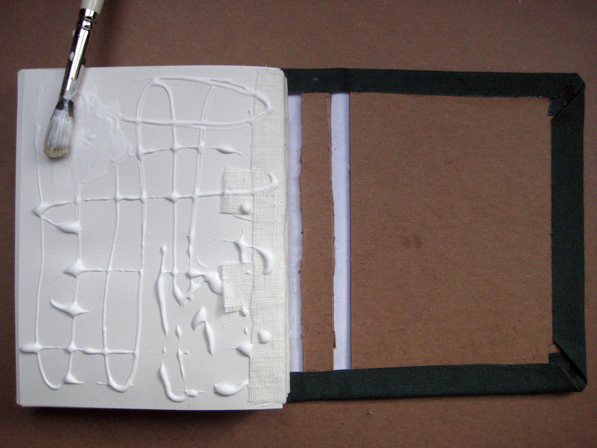 When the endsheets are dry, brush glue onto the enddsheet (it's helpful to do one side and then the other, rather than trying to glue both at once). Align the spine along the length of the cover. Do the same to the other side, gluing the other endsheet to