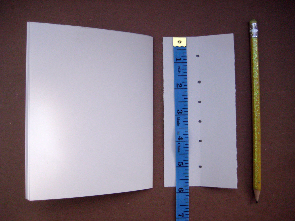 Take an extra sheet of (folded) paper whose spine is the same length as your signature. Along the fold, mark out six dots with your pencil: The first and last marks should be about 3/4 of an inch from the edge; the next two marks, each an inch inward from