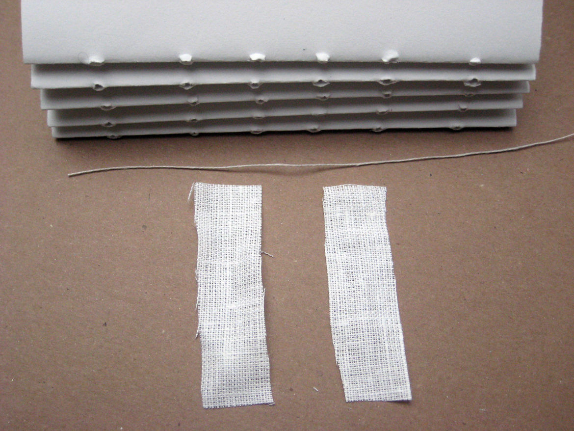 Measure out a length of thread that is as long as the spine times the number of signatures you plan to have. For example, our spine was six inches, times our five signatures, equals a 30-inch-long thread.<br /><br />In addition to the thread, cut two shor