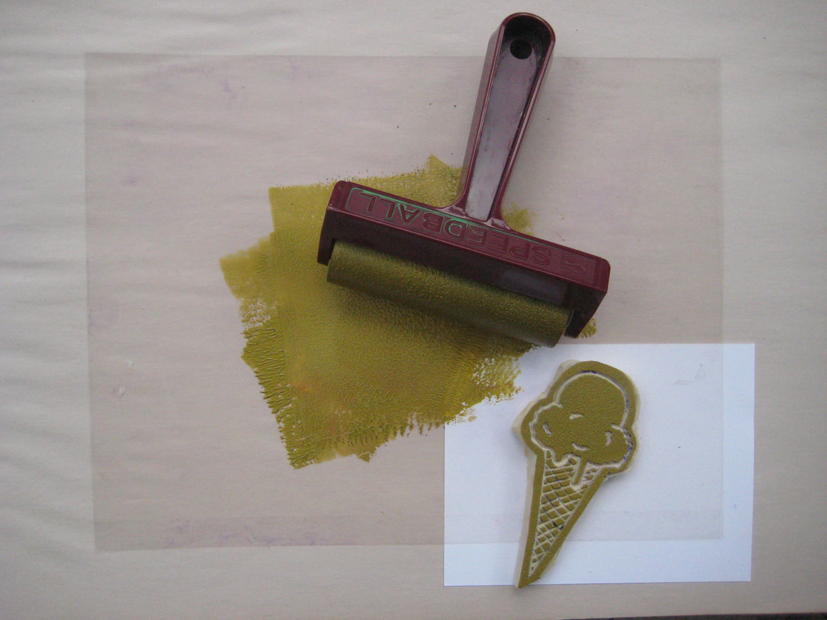 I use a transparency but you can probably use any non-porous, flat surface for the inking. Give a little squeeze of ink in the middle, roll the brayer around until it's covered, then roll it over your stamp. You can also see pretty clearly at this point i