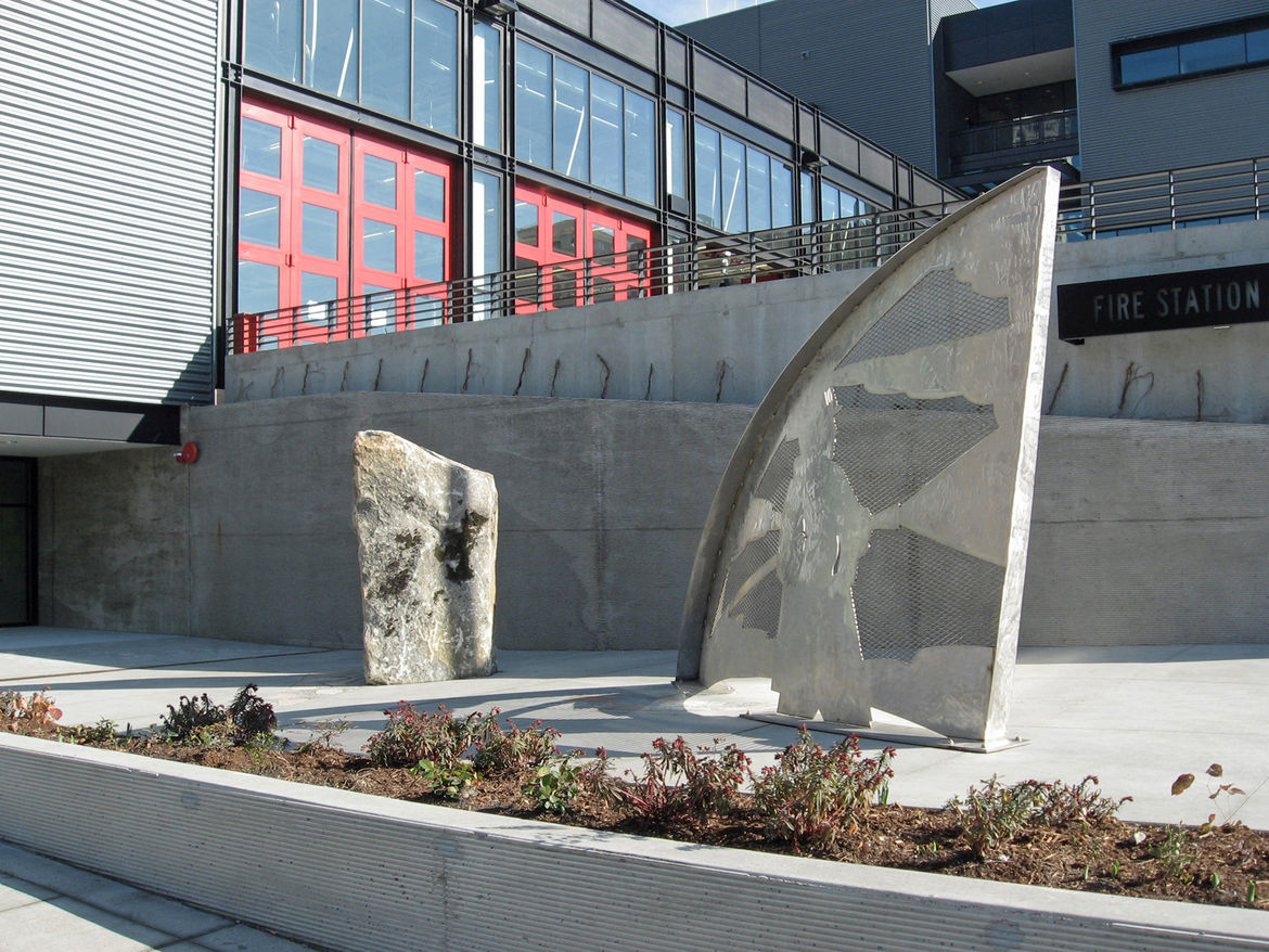 """<strong>""""Call and Response"""" by Stuart Nakamura</strong><br /><br /> Known in the Seattle Fire Department as """"the rock,"""" the large boulder's etched lines and the accompanying stainless steel arc invite water imagery for those entering Fire Station 10. Insi"""