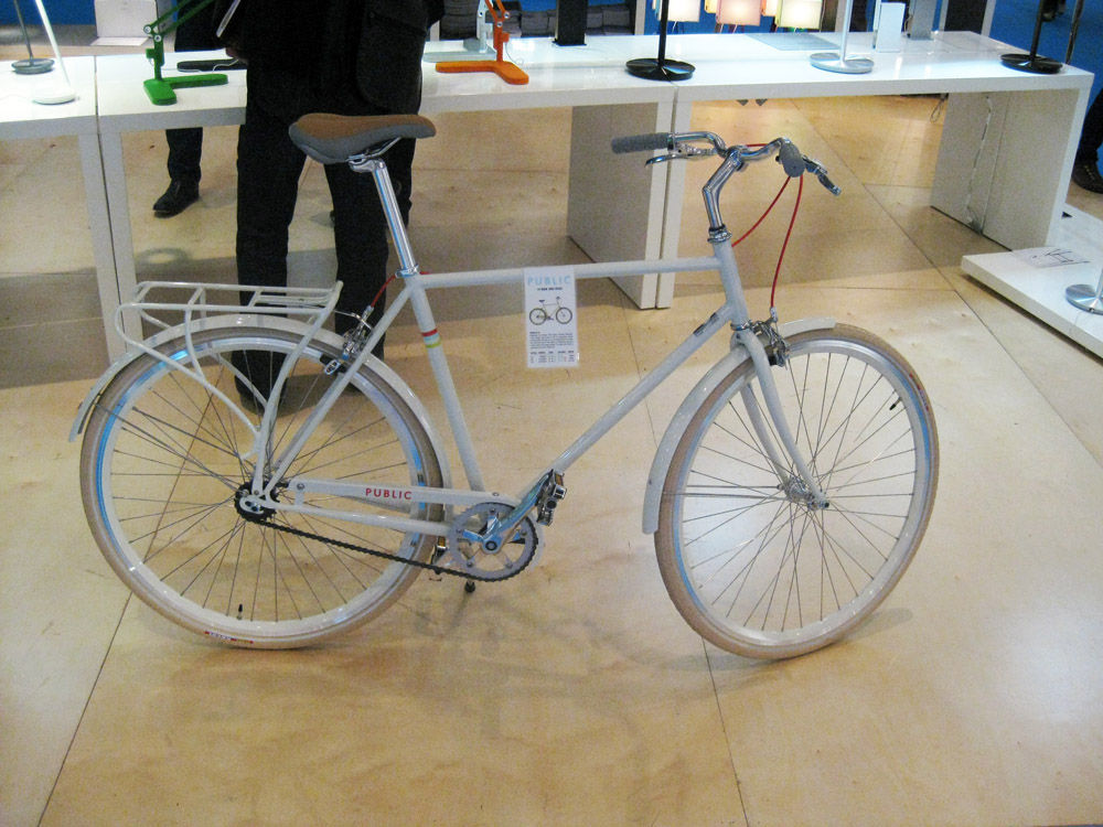"Back on the floor of the ICFF, PUBLIC bikes made cameos in a select number of booths. Here's a white Public D with a rear bicycle rack. The frame is a classic ""double diamond."""