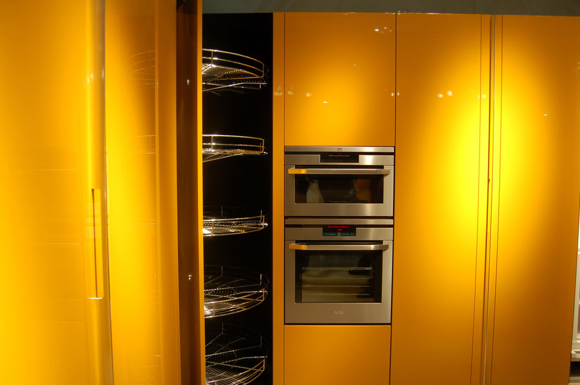 """Another shot of Cinquanta at <a href=""""http://www.berloni.it"""">Berloni</a> illustrates not only the lemon-yellowness of the lacquer but the pivoting Lazy Susan-like cupboard storage as well."""
