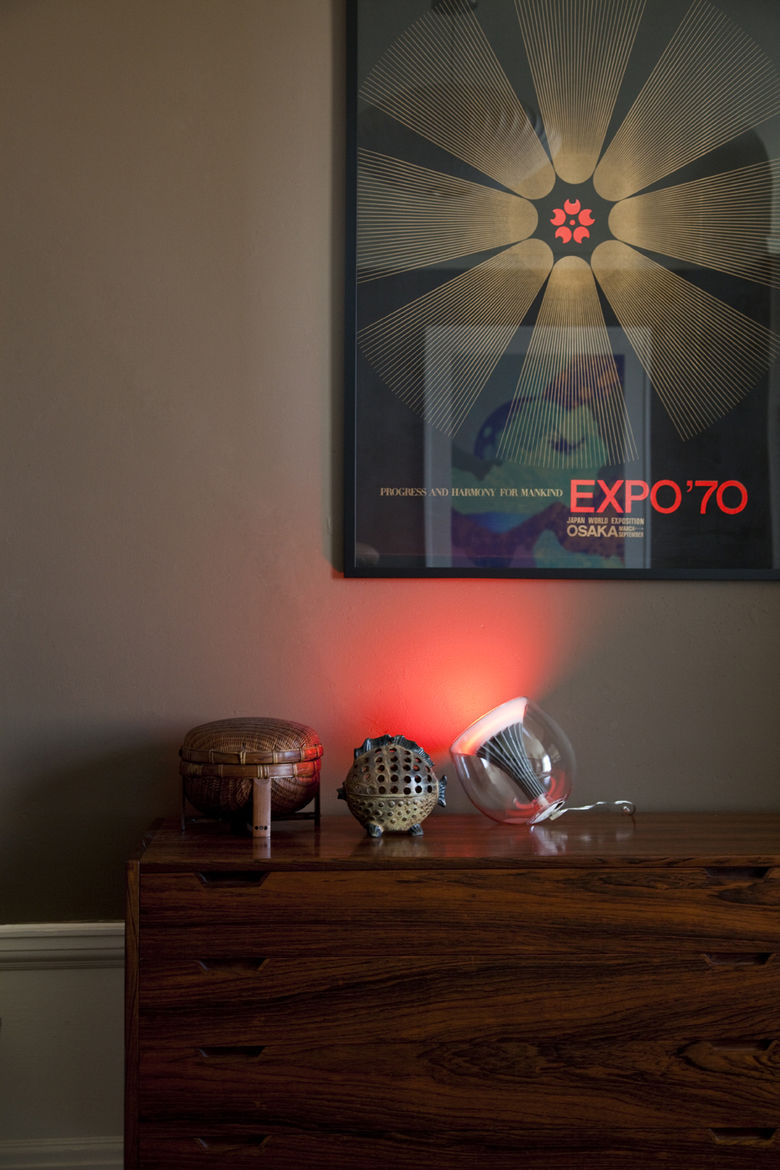 """A <a href=""""http://www.coloryourworldsweeps.com"""">LivingColors</a> lamp, resting next to a blowfish-shaped Japanese lantern, emits a concentrated beam of red light beneath a silk-screen print promoting Osaka's Expo '70."""