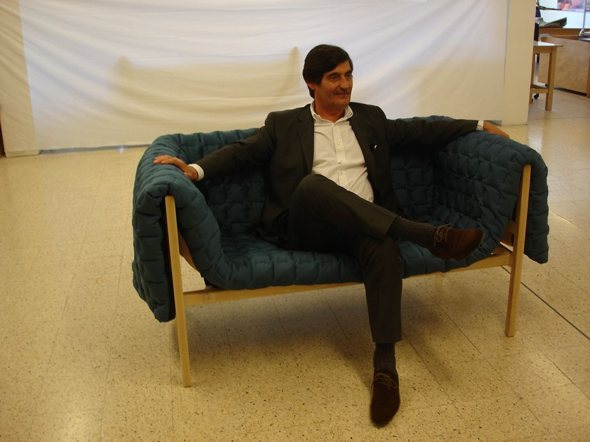 "Here's Michel Roset, CEO of Ligne Roset, sitting on ""one of the first prototypes built with the right wooden frame, draped in a cover made with the right stitch."""