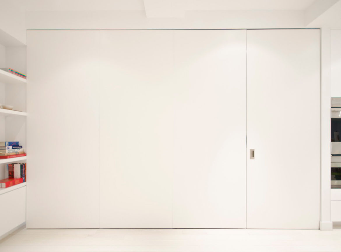 One of the home's boldest space-saving moves is this set of custom pivot-sliding doors, which offers the flexibility of a private room for guests without having to be permanently closed off from the rest of the apartment when not in use.