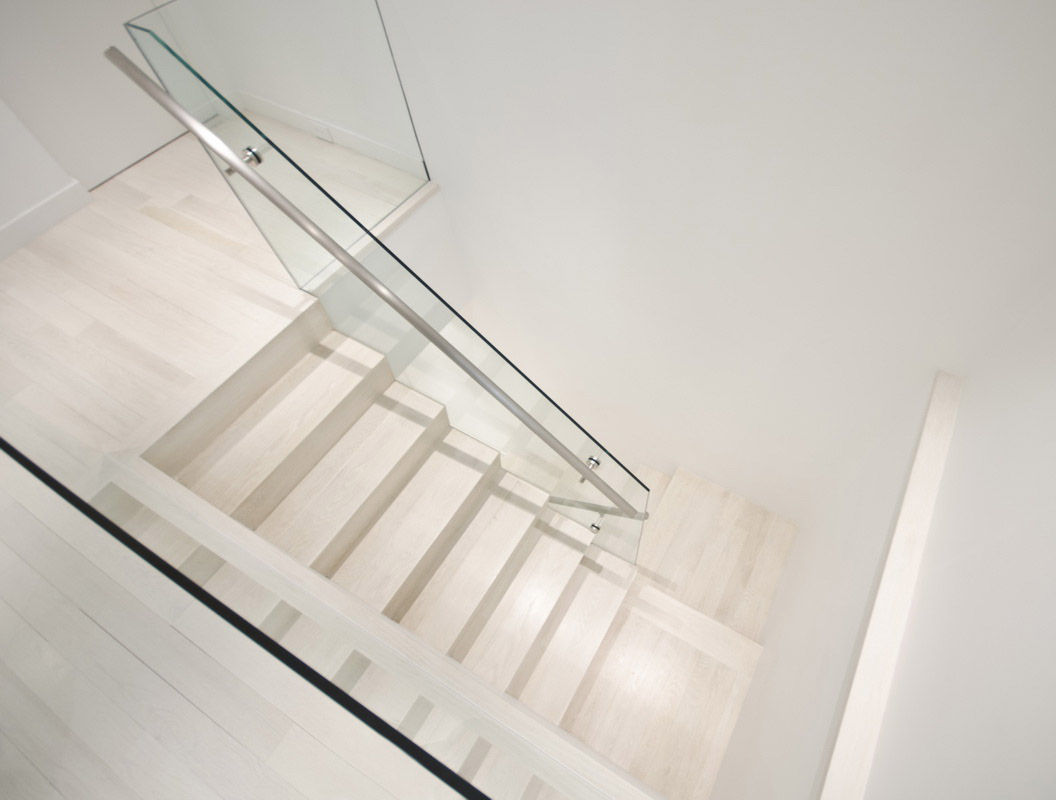 A stairwell featuring stainless-steel hand rails and glass connects the two levels.