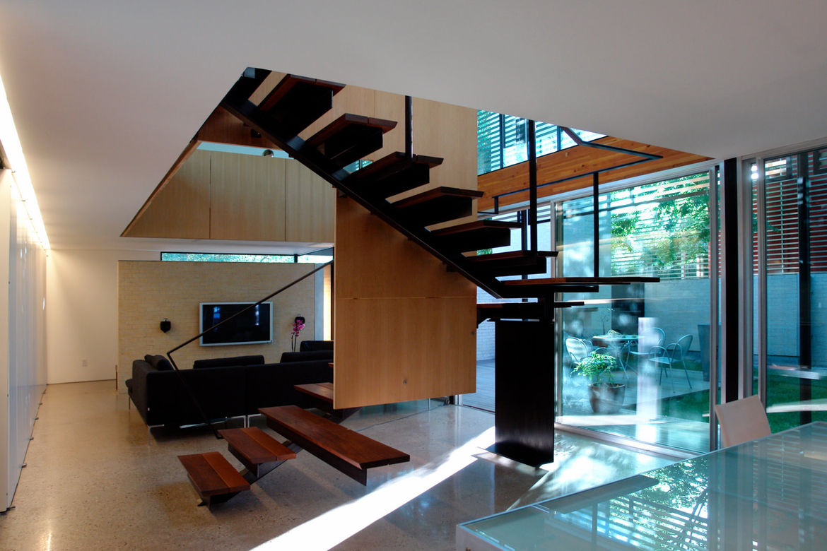The stairs to the second level are constructed with a steel superstructure and two-tone ipe treads. The third step from the bottom extends outward to form a bench.