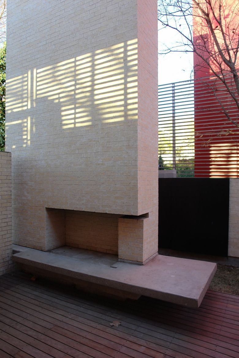 For cool nights in the courtyard, a built-in brick fireplace keeps outdoor space comfortable and functional.