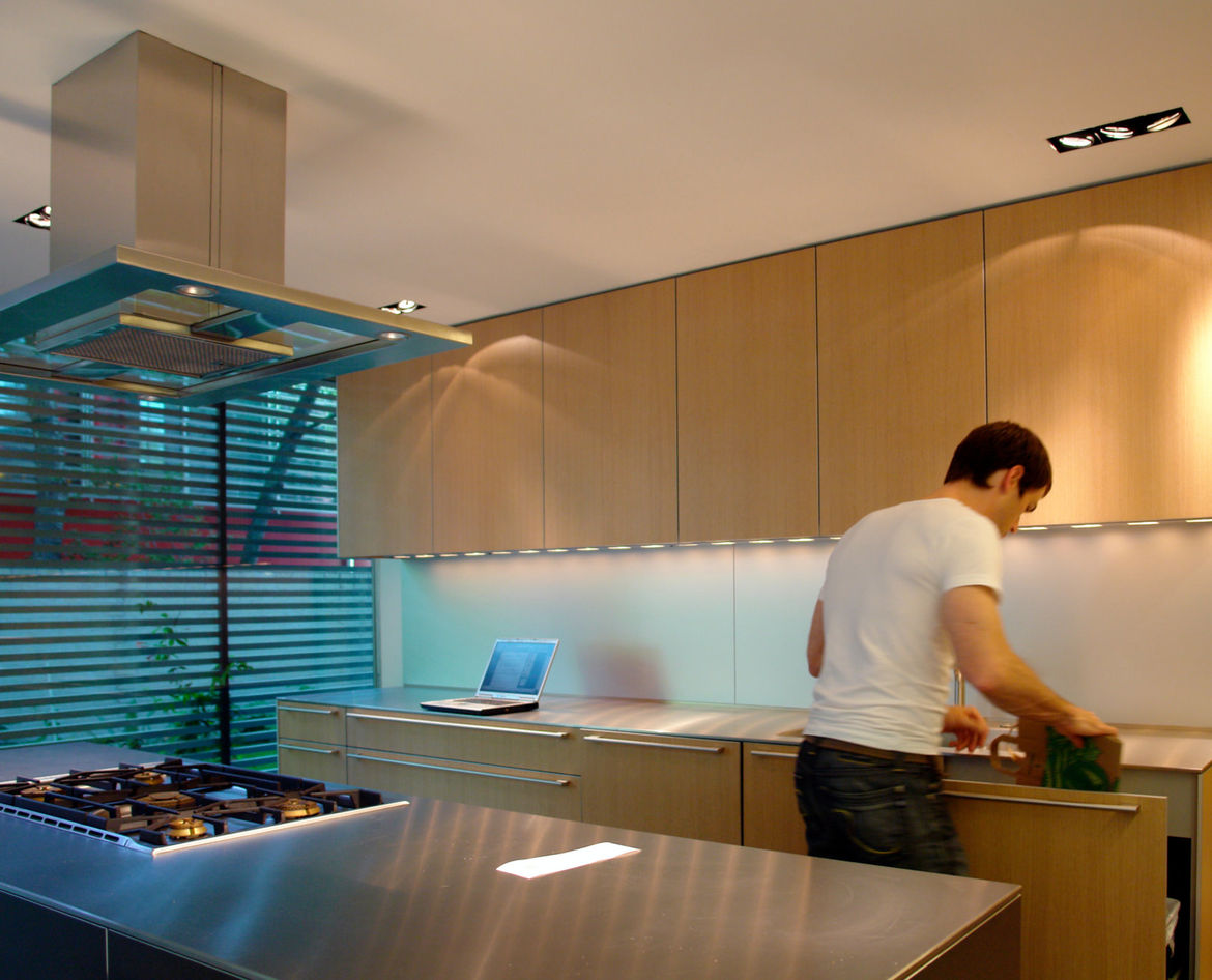 The Bulthaup kitchen is open and light, with a wide stainless steel countertop that separates the cooking area without isolating it from the living space, allowing the residents to prepare food while entertaining guests.
