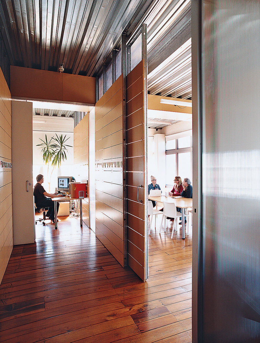 """A view of the building's third-floor offices, formerly the Bieringas' loft. The floors date from the building's days as a clothing factory. """"When we first moved in, I spent hours on my hands and knees pulling out carpet nails and sewing needles from the w"""