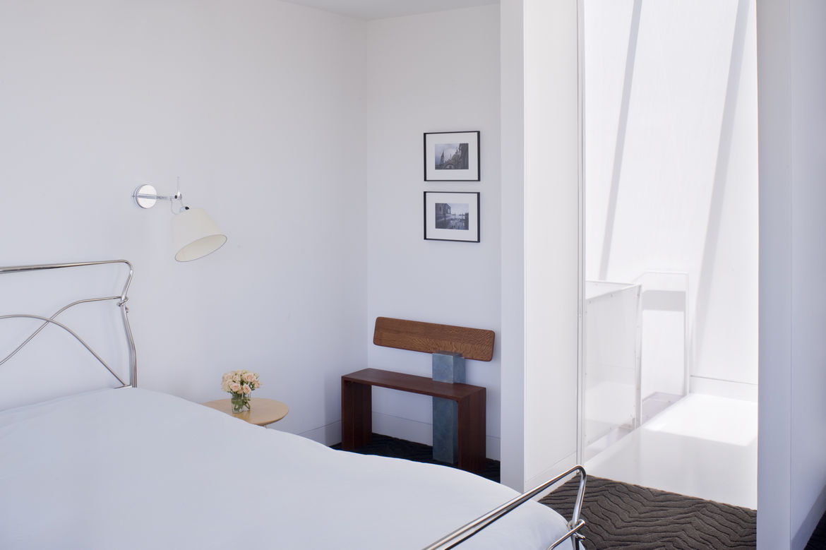 """Back in the master bedroom, the designers installed Tolomeo wall sconces by <a href=""""http://www.artemide.us/"""">Artemide</a> next to the bed and placed a bench next to the door made by Hart's uncle, Peter Czuk of <a href=""""http://www.czukstudio.com/"""">Czuk St"""