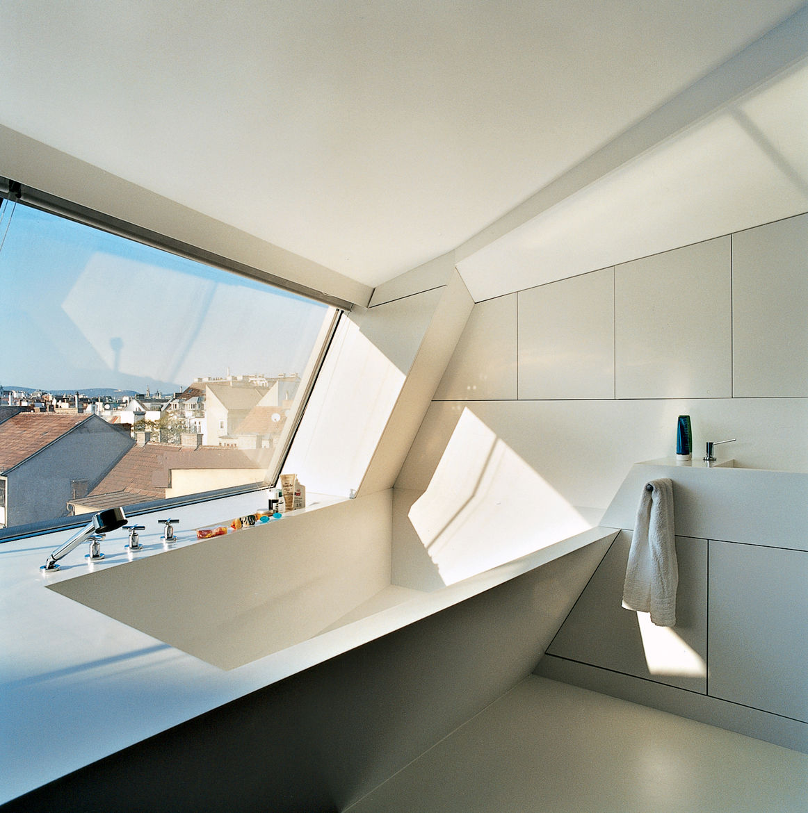 The cavity for the bathtub is part of the same continuous form-world as House Ray 1's sloping roofscape. The white tub is made from Corian; the faucet is by Dornbracht.