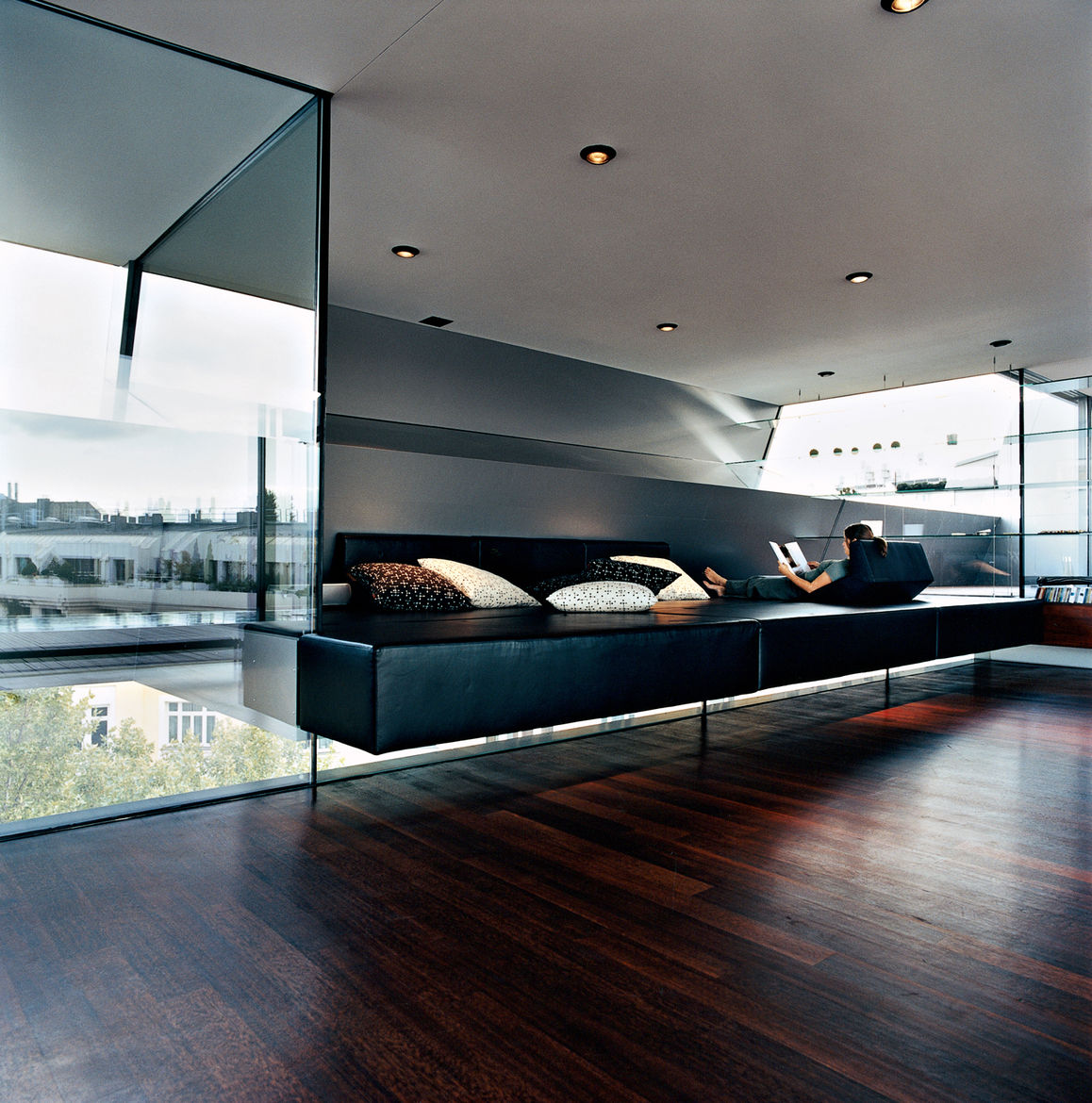 "Meissl and Delugan's favorite part of the house is definitely the ""relaxation zone,"" which features a black leather platform of their own design that appears to float between layers of tempered glass. The pillows are by Herman Miller."