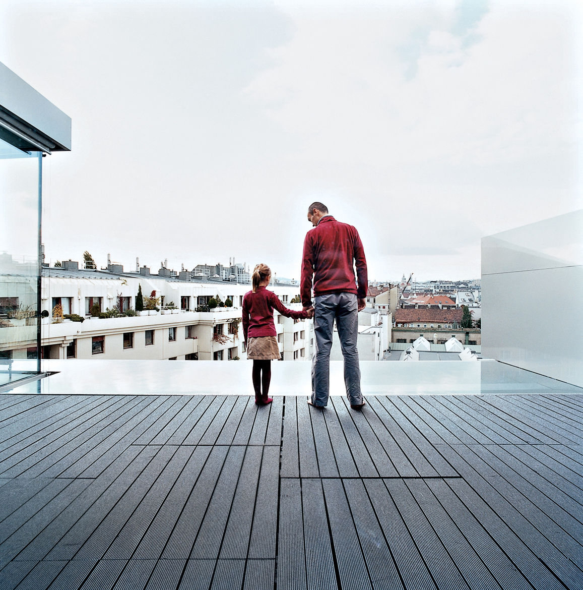 Roman and Nora stand on the terrace, and look out over the reflecting pool and beyond.