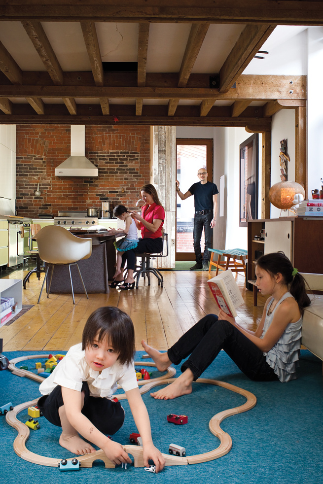 The house's open-plan layout encourages the entire family to hang out together, even while partaking in different activities. The durable area rug, made from carpet tiles by InterfaceFLOR, is the ideal base for both reading and playing with trains, as Luk