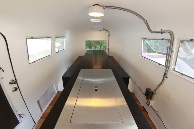 To maximize the small space inside the Airstream, Suzuki removed the existing structures and added a central island the follows his <i>kenchikukagu</i> style of design. Near the door (front of photo), a sink and cook top is hidden under the steel cover. A