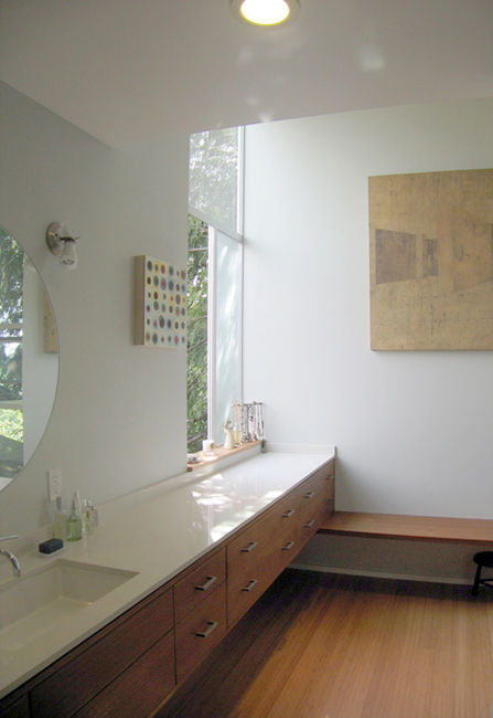 The view from the shower is oriented toward the corner focal point, where the dressing bench and sink counter meet and the window opens up to the outside.