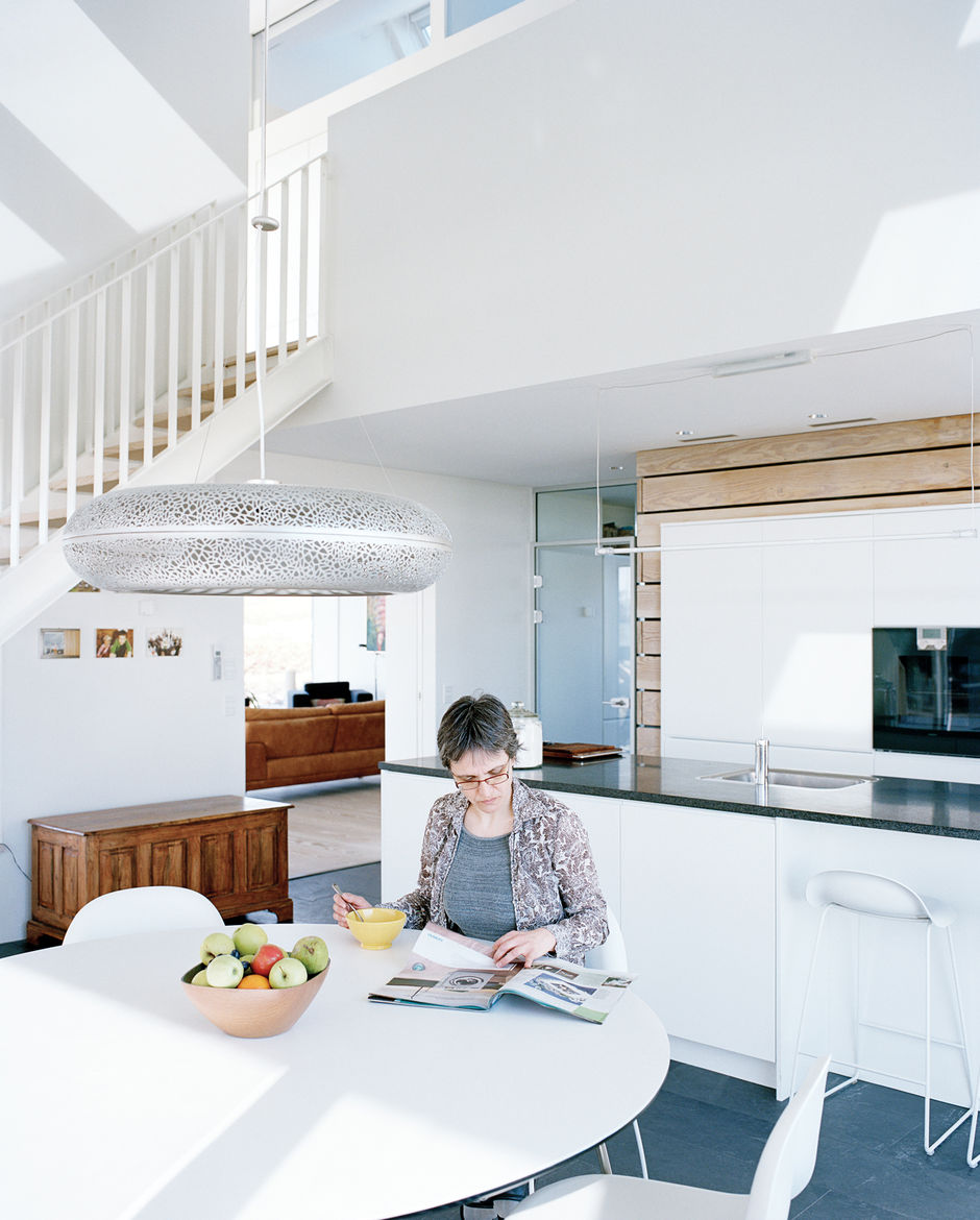 Sophie sits at the Nava dining table in the kitchen, which is flanked by Gubi chairs and illuminated by the Aeros light by Ross Lovegrove for Louis Poulsen.